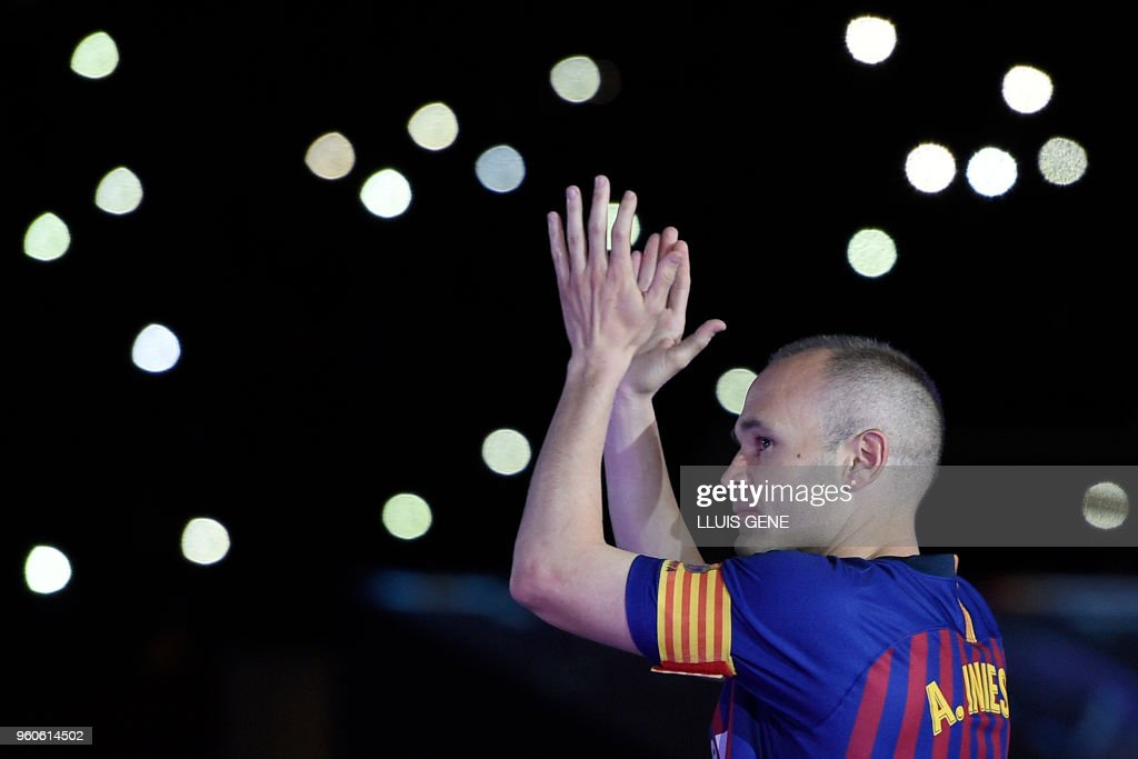 TOPSHOT - Barcelona's Spanish midfielder Andres Iniesta acknowledges fans during a tribute at the end of the Spanish league football match between FC Barcelona and Real Sociedad at the Camp Nou stadium in Barcelona on May 20, 2018. - Iniesta, who joined Barcelona's academy 22 years ago, played his final game for the club.