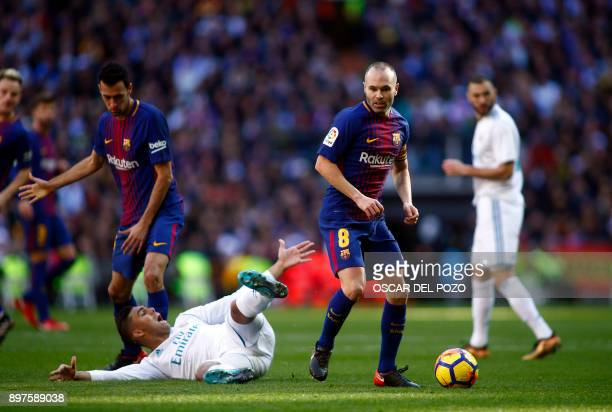 Barcelona's Spanish midfielder Andres Iniesta eyes the ball next to Real Madrid's Brazilian midfielder Casemiro during the Spanish League 'Clasico'...