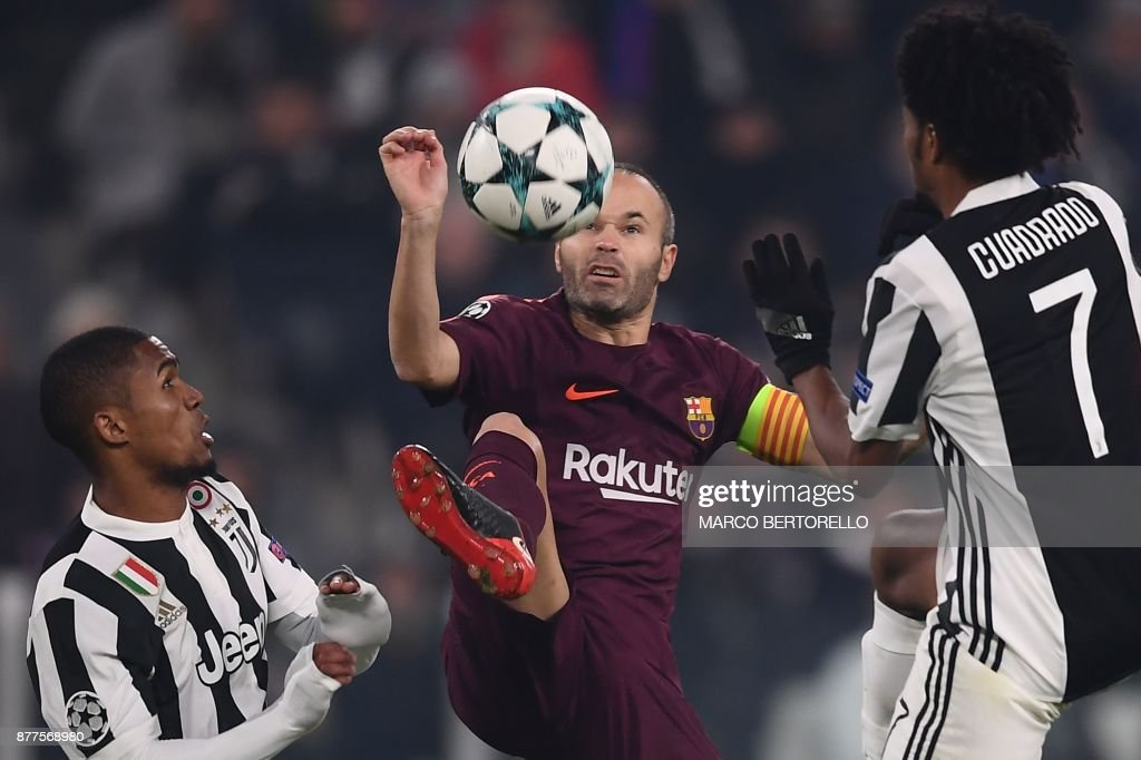 Barcelona's Spanish midfielder Andres Iniesta (C) fights for the ball with Juventus' forward from Brazil Douglas Costa and Juventus' forward from Colombia Juan Cuadrado (R) during the UEFA Champions League Group D football match Juventus Barcelona on November 22, 2017 at the Juventus stadium in Turin. / AFP PHOTO / Marco BERTORELLO