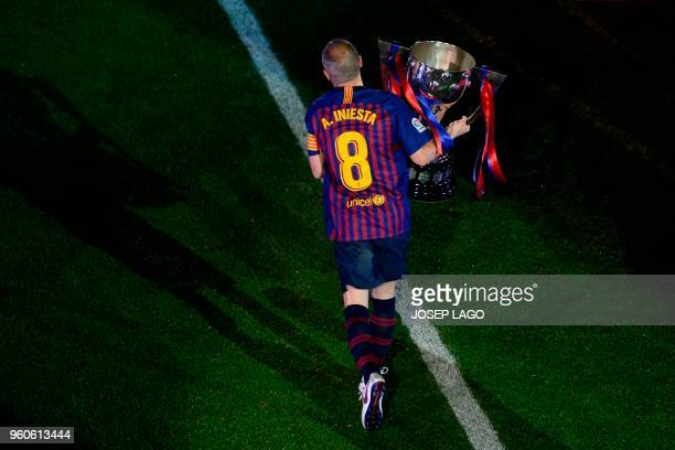 Barcelona's Spanish midfielder Andres Iniesta holds the Liga trophy during a tribute at the end of the Spanish league football match between FC...