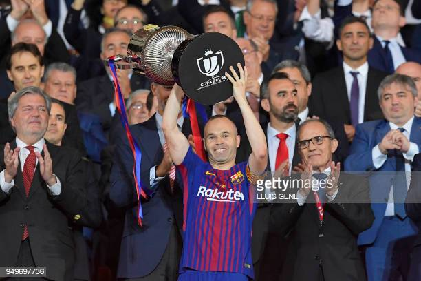 TOPSHOT Barcelona's Spanish midfielder Andres Iniesta holds the trophy after the Spanish Copa del Rey final football match Sevilla FC against FC...