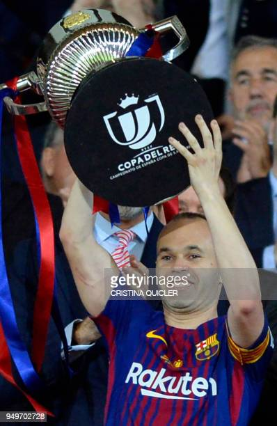 Barcelona's Spanish midfielder Andres Iniesta holds the trophy after the Spanish Copa del Rey final football match Sevilla FC against FC Barcelona at...