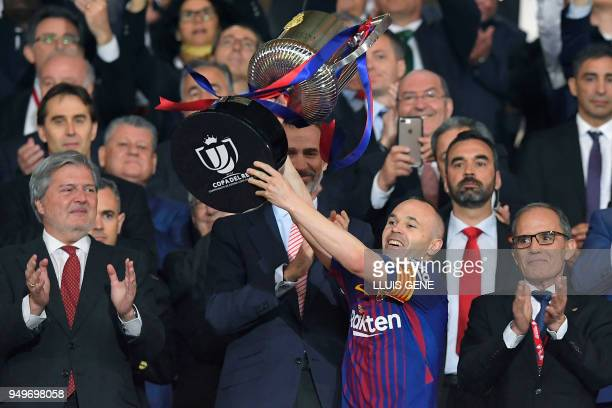 Barcelona's Spanish midfielder Andres Iniesta holds the trophy next to Spain's king Felipe VI after the Spanish Copa del Rey final football match...