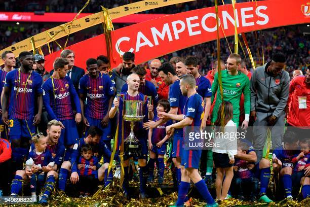 Barcelona's Spanish midfielder Andres Iniesta holds the trophy next to his teammates after the Spanish Copa del Rey final football match Sevilla FC...