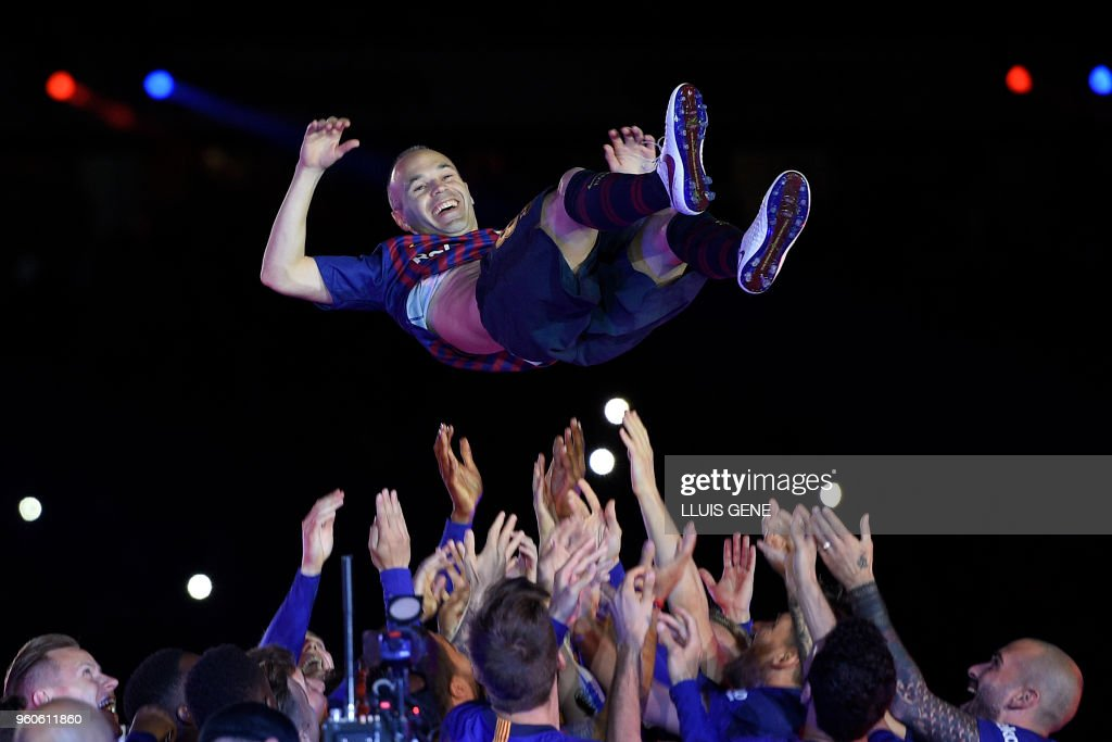TOPSHOT - Barcelona's Spanish midfielder Andres Iniesta is thrown in the air by teammates during a tribute after the Spanish league football match between FC Barcelona and Real Sociedad at the Camp Nou stadium in Barcelona on May 20, 2018. - Iniesta, who joined Barcelona's academy 22 years ago, played his final game for the club.