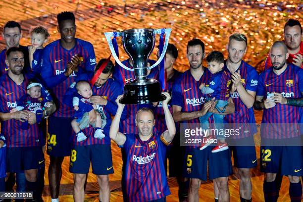 Barcelona's Spanish midfielder Andres Iniesta raises the Liga trophy during a tribute after the Spanish league football match between FC Barcelona...