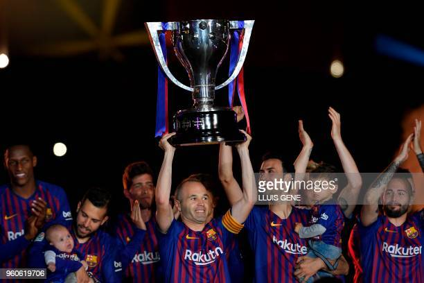 Barcelona's Spanish midfielder Andres Iniesta raises the Liga trophy during a tribute at the end of the Spanish league football match between FC...