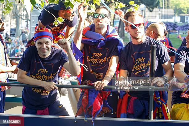 FC Barcelona's Spanish midfielder Andres Iniesta Spanish midfielder Sergio Busquets and Croatian midfielder Ivan Rakitic parade on a bus through the...