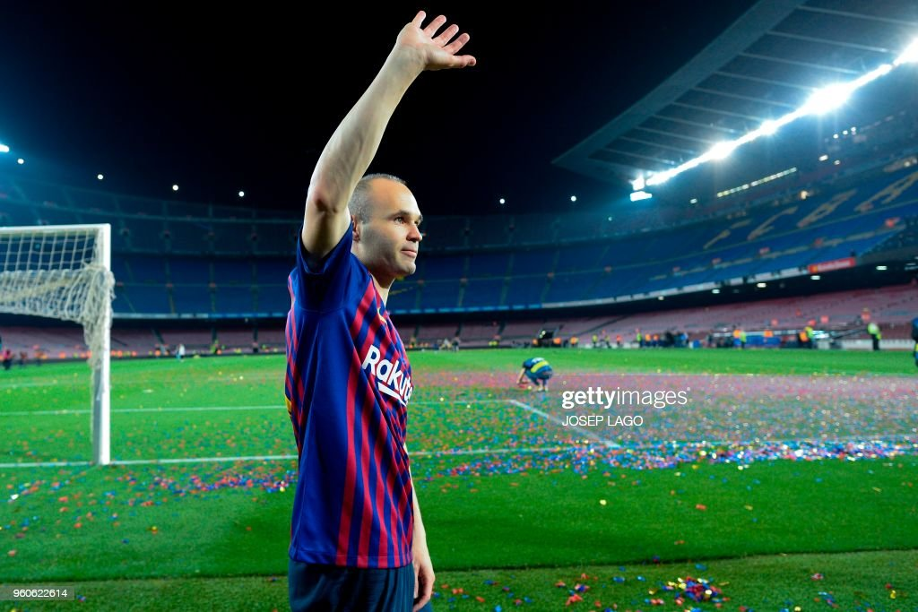 TOPSHOT - Barcelona's Spanish midfielder Andres Iniesta waves at the end of a tribute after the Spanish league football match between FC Barcelona and Real Sociedad at the Camp Nou stadium in Barcelona on May 20, 2018. - Iniesta, who joined Barcelona's academy 22 years ago, played his final game for the club.
