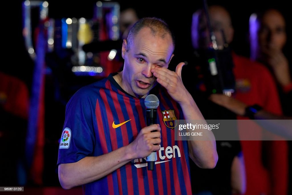 TOPSHOT - Barcelona's Spanish midfielder Andres Iniesta wipes his tears during a tribute after the Spanish league football match between FC Barcelona and Real Sociedad at the Camp Nou stadium in Barcelona on May 20, 2018. - Iniesta, who joined Barcelona's academy 22 years ago, played his final game for the club.