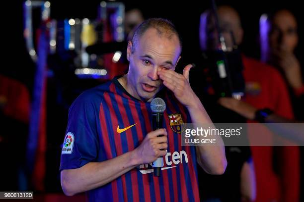 TOPSHOT Barcelona's Spanish midfielder Andres Iniesta wipes his tears during a tribute after the Spanish league football match between FC Barcelona...