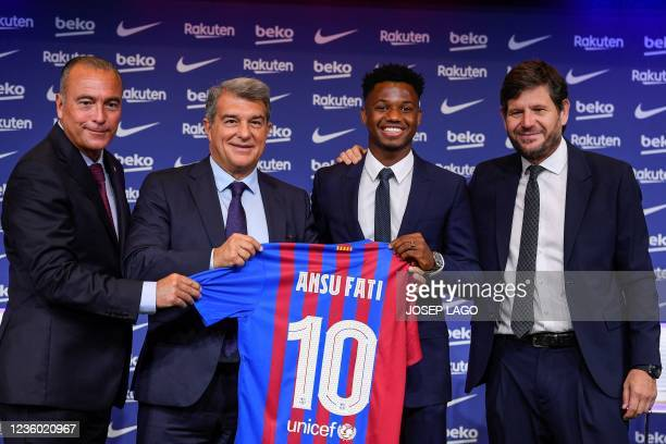 Barcelona's Spanish midfielder Ansu Fati poses for pictures holding his jersey with President of FC Barcelona Joan Laporta , FC Barcelona's first...