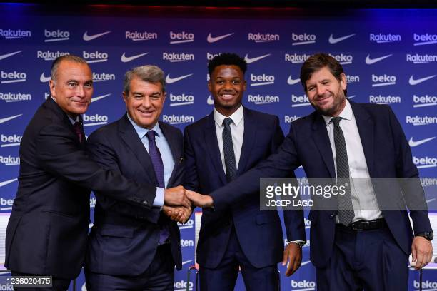 Barcelona's Spanish midfielder Ansu Fati poses for pictures with President of FC Barcelona Joan Laporta , FC Barcelona's first vice president Rafael...