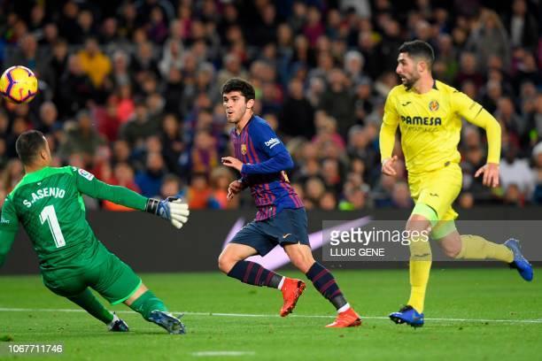 Barcelona's Spanish midfielder Carles Alena scores against Villarreal's Spanish goalkeeper Sergio during the Spanish league football match FC...