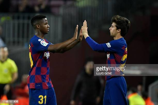 Barcelona's Spanish midfielder Riqui Puig replaces Barcelona's Guinea-Bissau forward Ansu Fati during the Spanish league football match between FC...