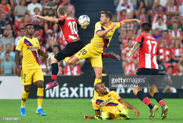 Barcelona's Spanish midfielder Sergi Roberto and Athletic Bilbao's Spanish forward Iker Muniain jump for a high ball during the Spanish league...