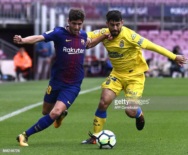 Barcelona's Spanish midfielder Sergi Roberto challenges Las Palmas' forward Pedro 'Tana' Tanasu during the Spanish league football match FC Barcelona...
