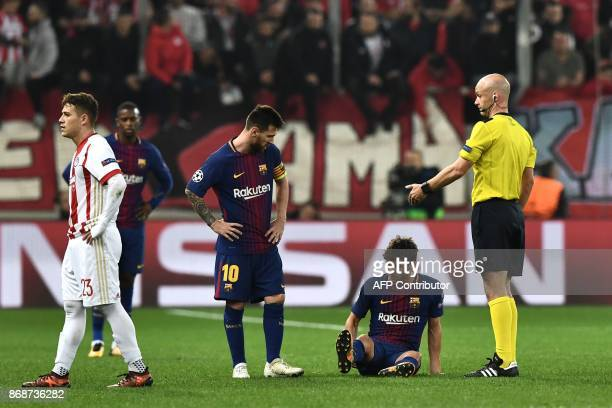 Barcelona's Spanish midfielder Sergi Roberto sits on the ground after an injury next to Barcelona's Argentinian forward Lionel Messi and British...