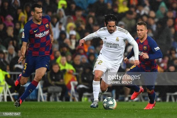 Barcelona's Spanish midfielder Sergio Busquets and Barcelona's Brazilian midfielder Arthur challenge Real Madrid's Spanish midfielder Isco during the...