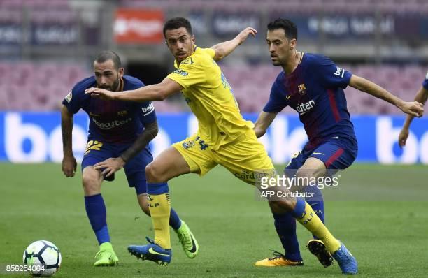 Barcelona's Spanish midfielder Sergio Busquets and Barcelona's Spanish defender Aleix Vidal challenge Las Palmas' Spanish midfielder Hernan Santana...