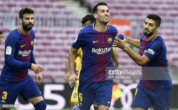 Barcelona's Spanish midfielder Sergio Busquets celebrates with Barcelona's Spanish defender Gerard Pique and Barcelona's Uruguayan forward Luis...