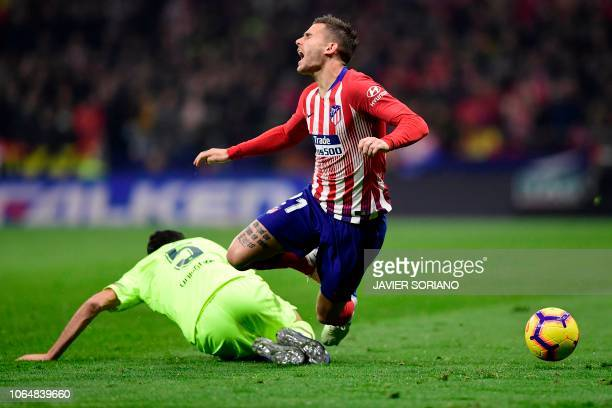 Barcelona's Spanish midfielder Sergio Busquets fouls Atletico Madrid's French defender Lucas Hernandez during the Spanish league football match...