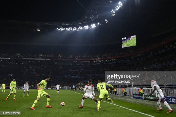 Barcelona's Spanish midfielder Sergio Busquets vies for the ball with Lyon's French forward Martin Terrier next to Barcelona's Portuguese defender...