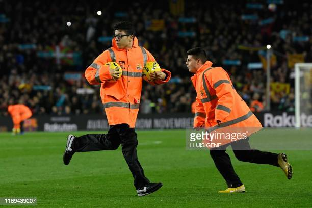 Barcelona's staff members grabs yellow footballs bearing the sentence Sit and talk during the El Clasico Spanish League football match between...