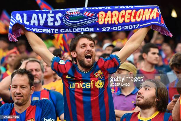 A Barcelona's supporter brandishes a scarf before the Spanish Copa del Rey final football match FC Barcelona vs Deportivo Alaves at the Vicente...
