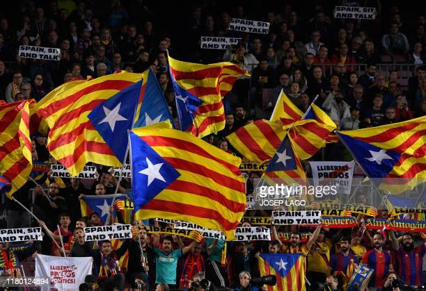 "Barcelona's supporters hold placards reading ""Spain, sit and talk"" and wave Catalan pro-independence ""Estelada"" flags from the stands during the UEFA..."