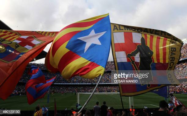 Barcelona's supporters wave a Estelada proindependent Catalonia flag between team flags during the Spanish league football match FC Barcelona vs UD...