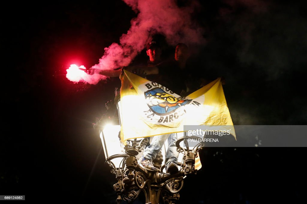 FC Barcelona's supporters wave a flare standing on a street lamp as they celebrate their team's 29th Copa del Rey title at the Canaletes fountain on Las Ramblas, in Barcelona on May 27, 2017 after the Spanish Copa del Rey (King's Cup) final football match FC Barcelona vs Deportivo Alaves at the Vicente Calderon stadium. Barcelona won 3-1. /