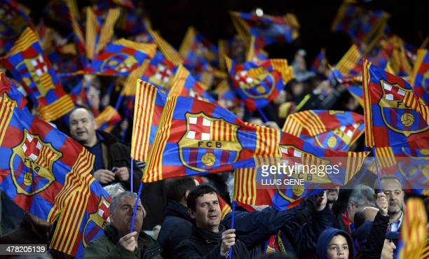 FC Barcelona's supporters wave their club's flag during the UEFA Champions League round of 16 second leg football match FC Barcelona vs Manchester...