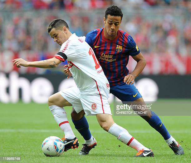 Barcelona's Thiago Alcantara and Porto Alegre's D'Alessandro challenge for the ball during their Audi Cup football match FC Barcelona vs SC...