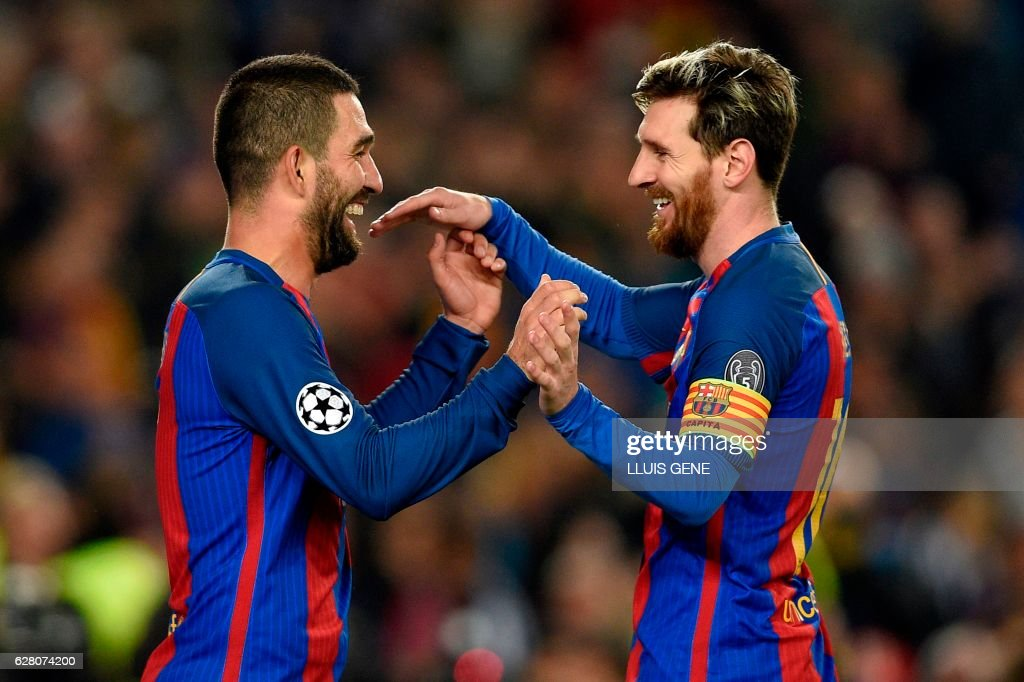 Barcelona's Turkish forward Arda Turan (L) celebrates with Barcelona's Argentinian forward Lionel Messi after scoring during the UEFA Champions League Group C football match FC Barcelona vs Borussia Moenchengladbach at the Camp Nou stadium in Barcelona, on December 6, 2016. / AFP / LLUIS