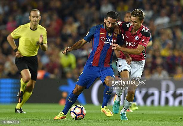 Barcelona's Turkish forward Arda Turan vies with Alaves' midfielder Marcos Llorente during the Spanish league football match FC Barcelona vs...