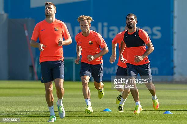 Barcelona's Turkish midfielder Arda Turan and Barcelona's Croatian midfielder Ivan Rakitic attend a training session at the Sports Center FC...