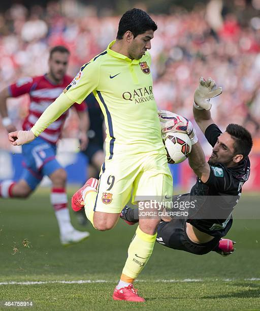 Barcelona's Uruguayan forward Luis Alberto Suarez vies with Granada's goalkeeper Oier Olazabal Paredes during the Spanish league football match...