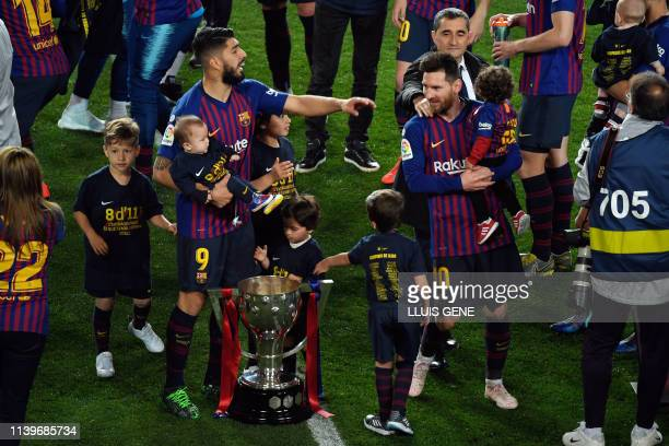 TOPSHOT Barcelona's Uruguayan forward Luis Suarez and Barcelona's Argentinian forward Lionel Messi with their children celebrate becoming La Liga...
