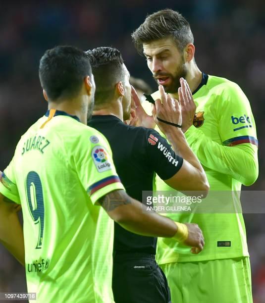 Barcelona's Uruguayan forward Luis Suarez and Barcelona's Spanish defender Gerard Pique speak with Spanish referee Carlos del Cerro Grande during the...