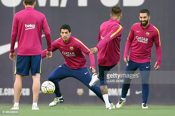Barcelona's Uruguayan forward Luis Suarez and Barcelona's Turkish midfielder Arda Turan take part with teammates in a training session at the Sports...
