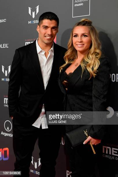 Barcelona's Uruguayan forward Luis Suarez and his wife Sofia Balbi pose on the red carpet during a photocall for Cirque du Soleil's latest show Messi...