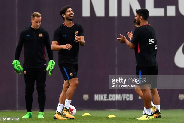 Barcelona's Uruguayan forward Luis Suarez applauds to Barcelona's Portuguese midfielder Andre Gomes during a training session at the Sports Center FC...
