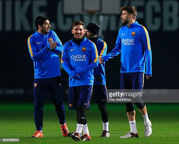 Barcelona's Uruguayan forward Luis Suarez Barcelona's Argentinian forward Lionel Messi and Barcelona's defender Gerard Pique joke during the first...