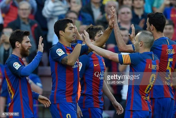 Barcelona's Uruguayan forward Luis Suarez celebartes a goal with teammates during the Spanish league football match FC Barcelona vs Villarreal CF at...