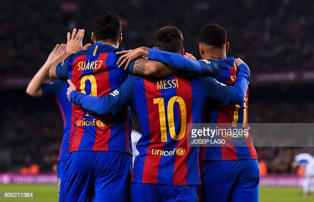 TOPSHOT Barcelona's Uruguayan forward Luis Suarez celebrates a goal with teammates Argentinian forward Lionel Messi and Brazilian forward Neymar...