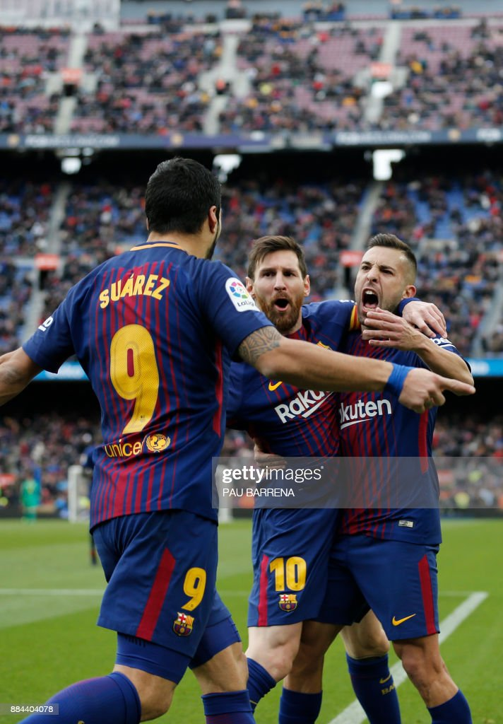 Barcelona's Uruguayan forward Luis Suarez (L) celebrates a goal with Barcelona's Argentinian forward Lionel Messi (C) and Barcelona's Spanish defender Jordi Alba during the Spanish league football match FC Barcelona vs RC Celta de Vigo at the Camp Nou stadium in Barcelona on December 2, 2017. / AFP PHOTO / Pau Barrena