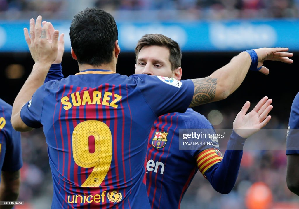 Barcelona's Uruguayan forward Luis Suarez celebrates a goal with Barcelona's Argentinian forward Lionel Messi (R) during the Spanish league football match FC Barcelona vs RC Celta de Vigo at the Camp Nou stadium in Barcelona on December 2, 2017. / AFP PHOTO / Pau Barrena