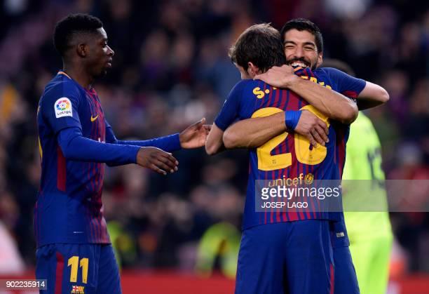 Barcelona's Uruguayan forward Luis Suarez celebrates a goal with Barcelona's Spanish midfielder Sergi Roberto as Barcelona's French forward Ousmane...