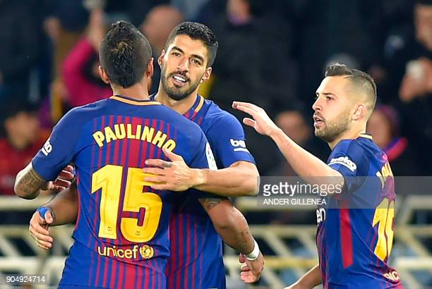 Barcelona's Uruguayan forward Luis Suarez celebrates a goal with Barcelona's Brazilian midfielder Paulinho and Barcelona's Spanish defender Jordi...